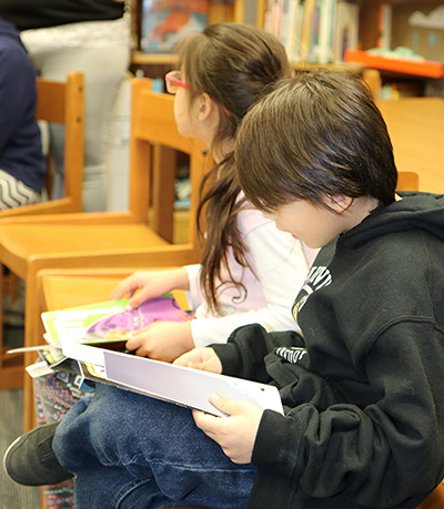 photo of boy and girl reading in library