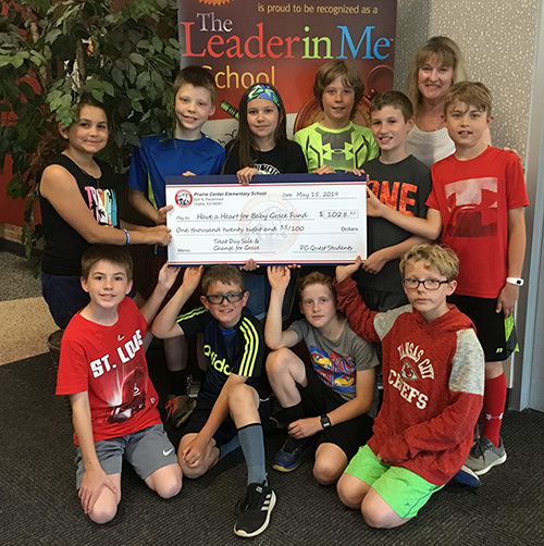 photo of students holding a big check